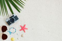 Top view of beach sand with coconut leaves, camera, bracelet made of seashells, sunglasses, shells and starfish. Beach background. Top view of beach sand with stock photos