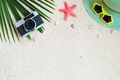 Top view of beach sand with coconut leaves, camera, shells, starfish, sunglasses, shells and straw hat. stock photos
