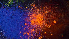 Top view of beautiful, bright colored powder falling and mixing. Dry orange and blue inks falling down on black. Background, art concept stock video footage