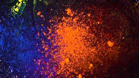 Top view of beautiful, bright colored powder falling and mixing. Dry orange and blue inks falling down on black. Background, art concept stock video