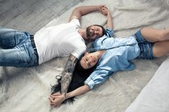 Top view of a beautiful couple laying over white background. girl with long dark hair. they are in love royalty free stock image