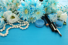 Top view of beautiful and delicate blue flowers arrangement next to pearls necklace and makeup Royalty Free Stock Image