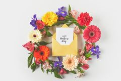 Top view of beautiful floral wreath and happy mothers day greeting card in envelope on grey royalty free stock photography
