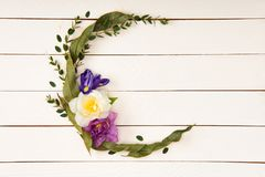 Top view of beautiful floral wreath with leaves and flowers. On wooden surface Royalty Free Stock Image
