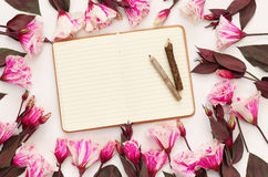 Top view of beautiful flowers and open blank notebook Royalty Free Stock Photography