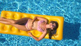 Top view of beautiful tanned girl in sunglasses and pink bikini lying on yellow inflatable mattress in swimming pool