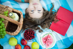 Top view of beautiful woman with picnic basket, fruits and book Royalty Free Stock Photography