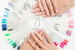 Top view of beautiful woman`s hands with collection of color nail polish samples on white background stock images