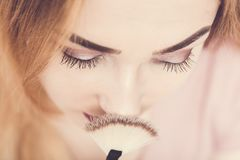 Top view of beautiful young girl face making makeup, fresh woman face with a brush near nose, cosmetics and beauty concept. Photo in pink pastel colors royalty free stock image