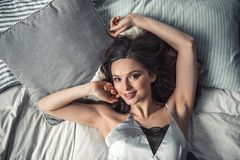 Girl in bed. Top view of beautiful young girl looking at camera and smiling while lying in bed at home Stock Photo