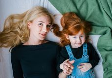 Top view of beautiful young mother and her little redhead daughter, looking at camera while lying in bed at home royalty free stock photo