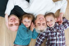 Top view of beautiful young parents, their cute little daughter and son looking at camera and smiling royalty free stock image