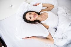 Top view of beautiful young woman holding hands behind pillow while lying in bed and smiling Stock Images