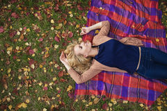 TOP VIEW: Beautiful young woman lies on a plaid in park in the fall Royalty Free Stock Photo