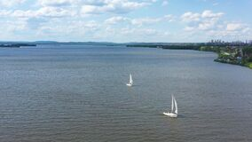 Top view of beautifully floating sailing yachts. Video. Sailing yachts float in lake on beautiful landscape with hilly