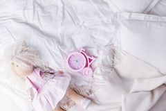 Top view bed with crumpled bed sheet, Good morning after a comfortable sleep. White pillow and blanket. Doll and alarm clock. Copy. Space stock image