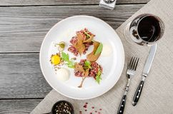 Top view beef tartar of raw minced meat restaurant served on white plate and glass of red wine on table, gray background. Space for text menu. Restaurant Stock Image