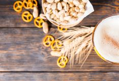 Top view of beer glass with a large head of foam near plate with. Pistachios, wheat, scattered small pretzels and peanuts on dark desk. Food and beverages Royalty Free Stock Photo