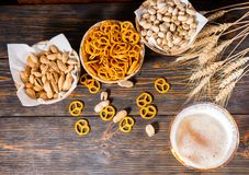 Top view of beer glass with a large head of foam near plates wit. H pistachios, small pretzels and peanuts on dark wooden desk. Food and beverages concept Royalty Free Stock Photos