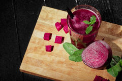 Top view of a beet beverage in a glass. Cut red beetroots and greens on a black table background. Healthy smoothies. Royalty Free Stock Image