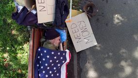 Top view of a beggar lying on bench, covered with flaf of USA. Homeless man begging for money on board with sign need money stock video