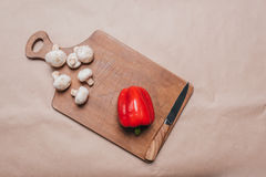 Top view of bell pepper and mushrooms with knife laying on wooden board Royalty Free Stock Images