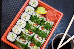 Top view of bento to-go plastic box, mixed nigiri and assorted sushi roll in lunch box place on wooden background. Philadelphia rolls with salmon, cheese and Royalty Free Stock Image