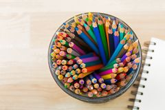 Top view of big glass full of coloring colored pencils with blur stock photography