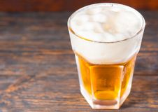Top view of big glass with a light beer and a large head of foam. On old dark desk. Drink and beverages concept Stock Photography