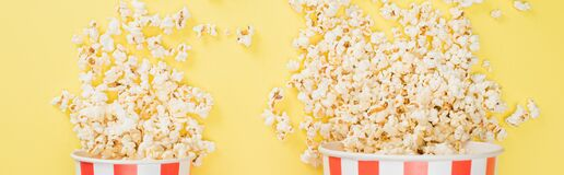 top view of big and small buckets with crunchy popcorn on yellow, banner, cinema concept.