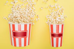 top view of big and small buckets with tasty popcorn on yellow, cinema concept.