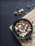 Top view of black bowl with nuts and dried fruits on the wooden cutting board with black chalkboard background. royalty free stock photo