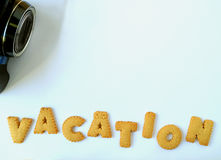 Top view of black camera and the word VACATION, made with alphabet shaped biscuits on pale blue table, with free space for text Royalty Free Stock Images