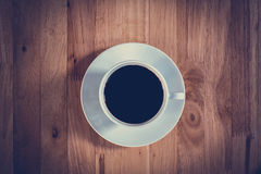 Top view of black coffee in the cup on wooden table Royalty Free Stock Images