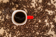 Top view of black coffee in red cup on burlap sack background Stock Image