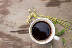 Top view of Black coffee in a white cup with grass flower on wooden. Black coffee in a white cup with grass flower Stock Image