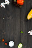 Top view of black desk being empty in center. Add some details. Yellow bottle lying between pepper and mushroom, little pieces of leaves lying in the middle Royalty Free Stock Images