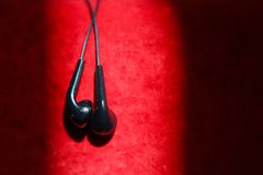 Top view of black earphones on a red velvet texture background. concept lifestyle. hight contrast colors. Top view of black earphones on a red velvet texture royalty free stock photo