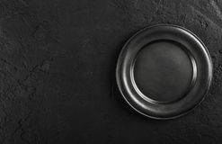 Top view of black empty plate on black stone background. Flat lay stock images