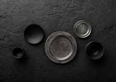 Top view of black and grey empty plates and bowls on black stone background royalty free stock photos