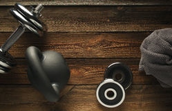 Top view of black iron kettlebell, dumbbell and grey towel on wo. Oden floor Sport background with copyspace  Healthy diet and fitness concept Royalty Free Stock Photography