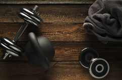 Top view of black iron kettlebell, dumbbell and grey towel on wo. Oden floor Sport background with copyspace  Healthy diet and fitness concept Stock Images
