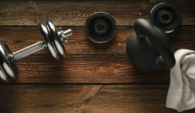 Top view of black iron kettlebell, dumbbell and white towel on w. Ooden floor Sport background with copyspace  Weight lifting exercise concept Royalty Free Stock Photography