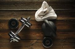 Top view of black iron kettlebell, dumbbell and white towel on w. Ooden floor Sport background with copyspace  Weight lifting exercise concept Stock Photo