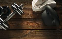 Top view of black iron kettlebell, dumbbell and white towel. On wooden floor Sport background with copyspace  Weight lifting exercise concept Stock Photo
