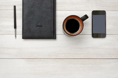 Top view of black notebook and pen with cup hot coffee Royalty Free Stock Photography