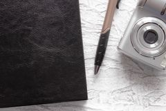 Top view of black notebook and pen near photo camera on white desk background for mockup royalty free stock images