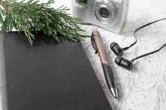 Top view of a black notepad with a green sprig and pens next to the camera and headphones on a white table stock photo