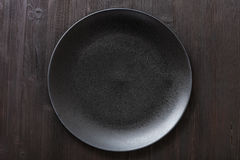 Top view of black plate on dark brown table Royalty Free Stock Photography