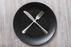 Top view of black plate with flatware on gray Royalty Free Stock Photo